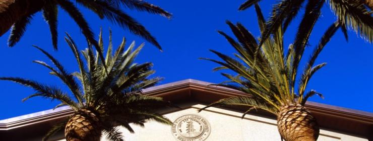Stanford Alumni Hall - tall, tan building with pointed roof framed by palm trees