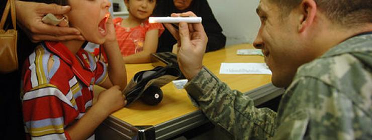 man dressed in military fatigues shines light into child's mouth as part of medical examination