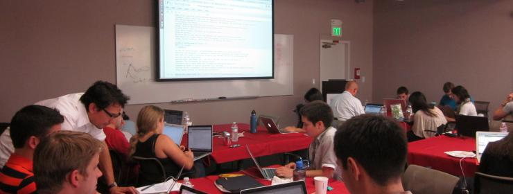 conference room full of students working on laptops as part of a workshop class