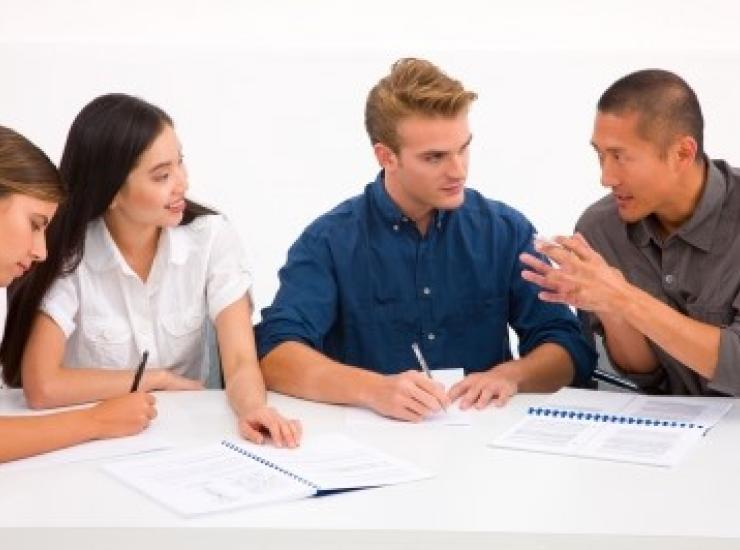 group of college students talk at a table