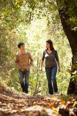 man and woman walking on path in forest engaged in conversation