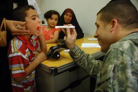 man dressed in green military fatigues shines a flashlight in a child's mouth as part of a medical examination