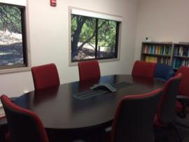 small conference room with six red wheeled chairs and bookshelves