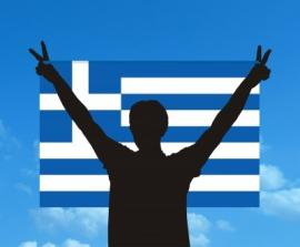 man standing in front of greek flag