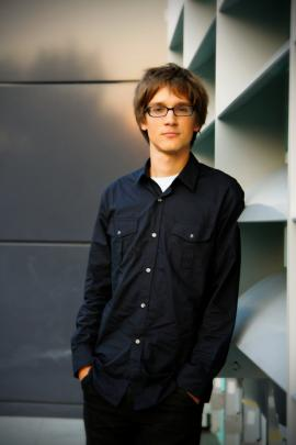 young man with short brown hair and glasses next to bookcase