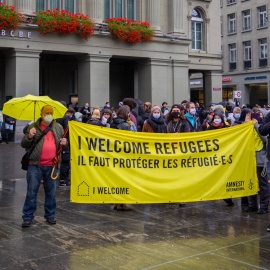 People holding sign that welcomes refugees