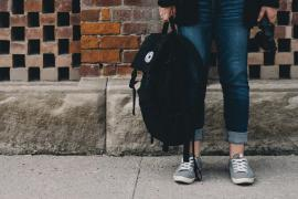 student holding backpack in front of brick wall