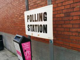 "sign reading ""polling station"" in front of brick wall"