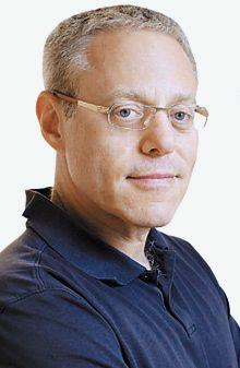 man with light colored short hair and glasses in blue polo shirt