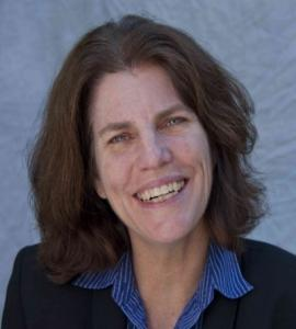 woman with shoulder-length brown hair in suit with blue shirt