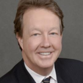 man with short brown hair in a black suit