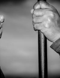 hands gripping jail bars as if from the inside of a jail cell